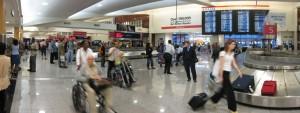 Rollstuhlfahrer und Begleiter vor Gepäckausgabe am Flughafen