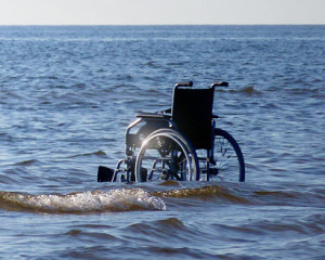 Leerer Rollstuhl im Meer an Ufernähe