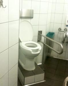 Toilette auf deutlich zu hohem Sockel.