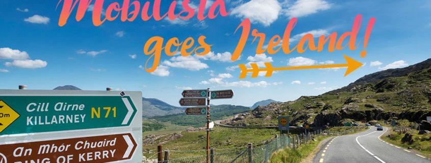 Irische Landschaft mit Straßen und Wegweisern, Beschriftung: Mobilista goes Ireland!