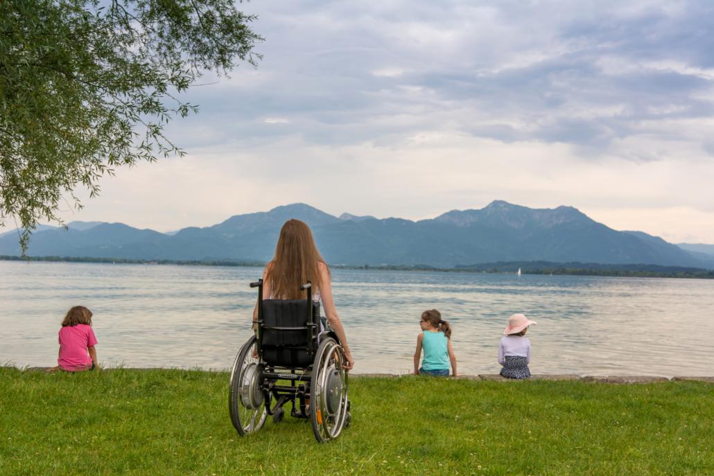 Rollstuhlfahrerin am Chiemseestrand mit Kindern
